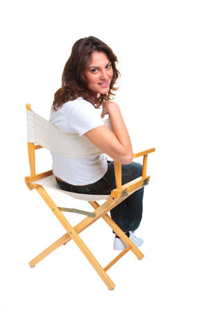 A brunette woman in casual clothing sat on a directors chair looking back over her shoulder, isolated on a white background. photo