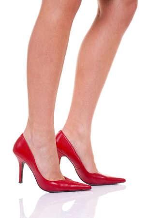Un womans las piernas con zapatos de tacón altos rojos, aislados en un fondo blanco.
