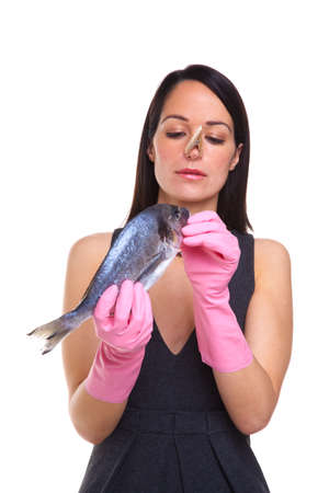 A woman wearing rubber gloves holding a raw fish, isolated on a white background Stock Photo - 6444201