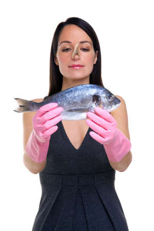 A woman wearing rubber gloves with a clothes peg on her nose holding a fish out in front of her, focus is on her face. photo