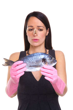 preperation: A woman wearing rubber gloves holding a raw fish, isolated on a white background