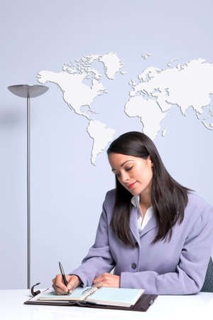 A businesswoman sat at her office desk writing, world map on the wall behind her. Stock Photo - 6444183