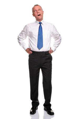 tiresome: A mature businessman with his hands on his hips yawning, isolated on a white background.
