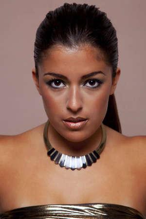 Headshot of a beautiful brunette woman wearing a gold neckalace and top. Stock Photo - 6444220