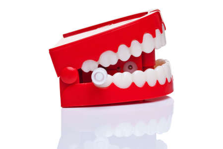 A pair of joke wind up chattering teeth on a pure white background. photo