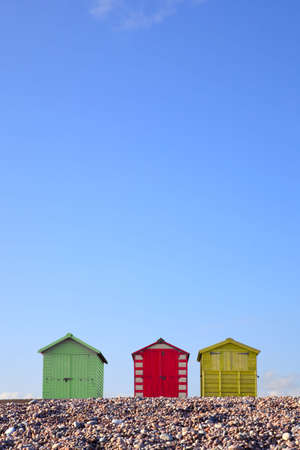 huts: Three colourful beach huts against a bright blue sky, framed to allow copy space in the upper part of the image.