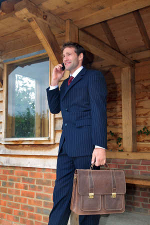 Businessman in his late twenties standing at a rural bus stop talking on his mobile phone photo