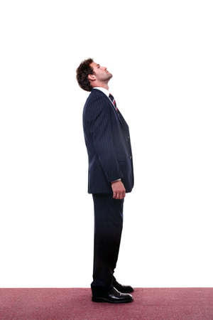 Chupito de longitud completa de un hombre de negocios looking up alta.