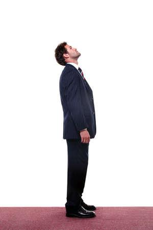 ascending: Chupito de longitud completa de un hombre de negocios looking up alta.