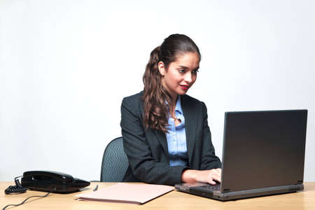 Young businesswoman sat at a desk typing on a laptop computer Stock Photo - 6444214