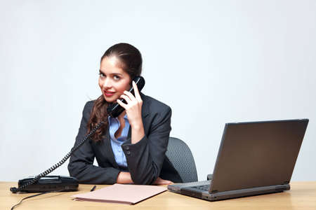 Young businesswoman sat at a desk talking on the telephone Stock Photo - 6444213