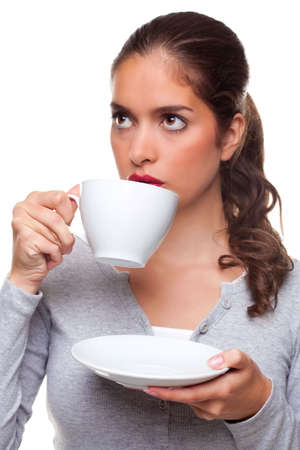 A woman drinking tea from a cup and saucer as she is thinking about something, white background. Stock Photo - 6444227