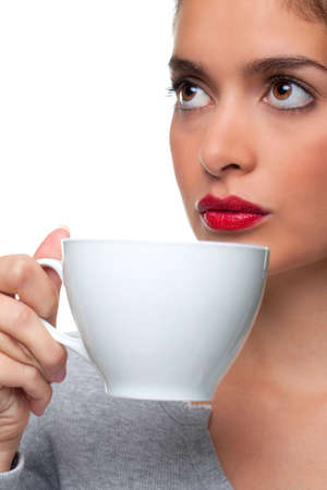A woman holding a white cup about to drink some tea as she is thinking about something, white background. Stock Photo - 6444210