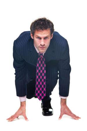 Imprenditore in una posizione di partenza, isolato su uno sfondo bianco.