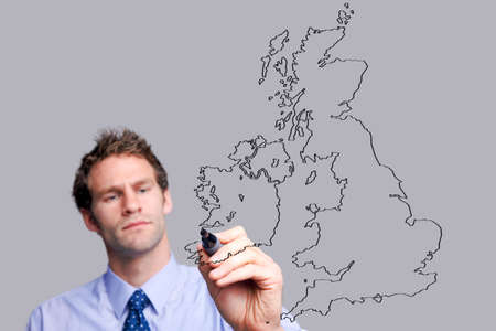 uk map: Businessman drawing a UK map on a glass screen, add your own text. The background is a uniform color all over so you can increase the copy space easily. Focus is on his hand and pen.