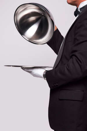 serving tray: Butler lifting the cloche from a silver serving tray, insert your own object onto the tray.