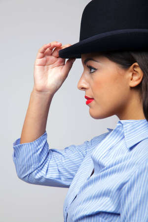 Side view of a businesswoman touching the rim of a bowler hat she is wearing. photo