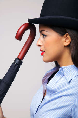 Side view of a businesswoman wearing a bowler hat and holding an umbrella. Stock Photo - 6444196