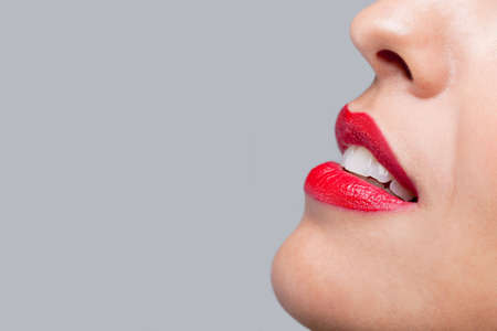 Close up of a womans face with bright red lipstick on her lips. photo