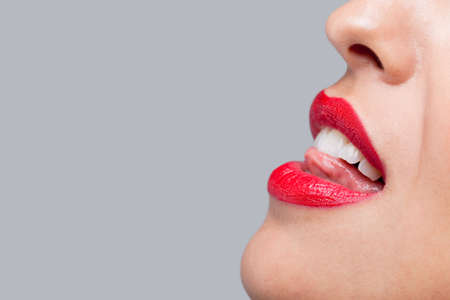 Close up of a womans face with bright red lipstick licking her teeth. Stock Photo - 6444179