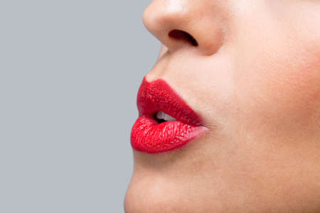 Close up of a womans face with red lipstick on blowing a kiss photo