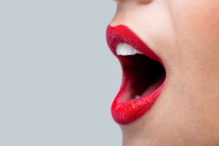 Close up of a womans mouth wide open with bright red lipstick on her lips. Stock Photo