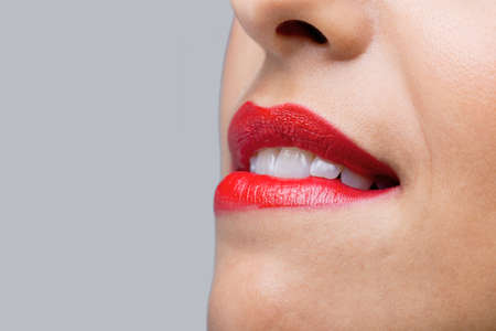Close up of a womans face with bright red lipstick biting her lips. photo
