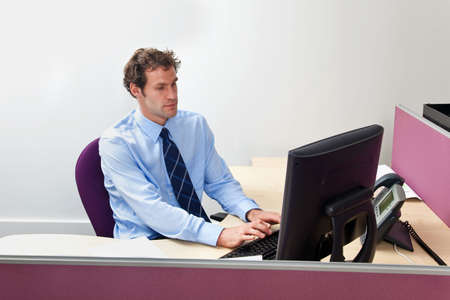 A male office worker sat at his desk working on a computer  photo