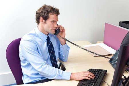 answering phone: Un trabajador de oficina masculino responder el tel�fono y mirando un equipo monitor en un centro de servicio al cliente. Foto de archivo