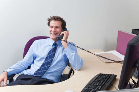 A businessman wearing shirt and tie sat at his desk chatting on the telephone. Stock Photo - 6444238