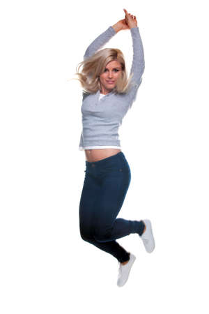 A pretty young blond woman jumping in the air, isolated on a white background. Slight motion blur. Stock Photo - 6444130