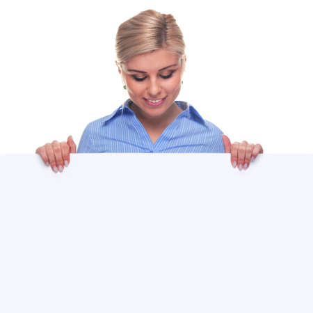 An attractive blond woman looking down at the blank sign she is holding, the board is a uniform color so you can make it larger if you wish to add your own image or message.