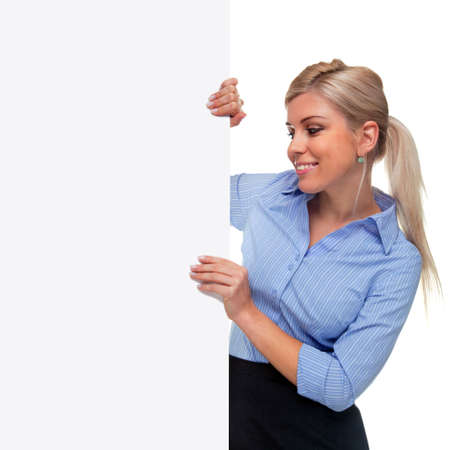 An attractive blond woman holding the side of a blank billboard looking at the blank space, the board is a uniform color so you can make it larger if you wish to add your own image or message. photo