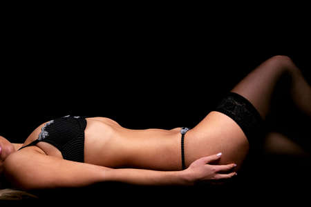 A slim woman lying on a black background wearing black lingerie and stockings. photo