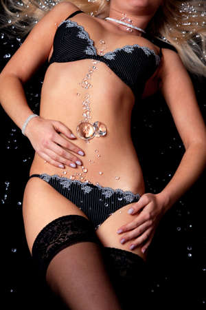 A woman wearing black lingerie and stockings covered in diamonds lying on a black background. photo
