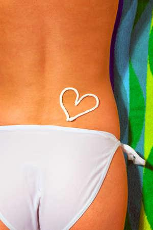 Lower half of a woman sunbathing wearing white bikini bottoms with a suntan cream drawing of a heart on her back Stock Photo - 6444246