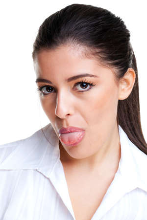 blowing out: Brunette woman in her twenties looking towards camera sticking her tongue out Stock Photo