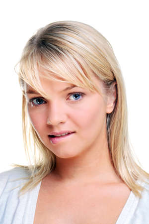 An attractive blond woman in her twenties looking towards camera biting her lip, natural blue eyes. Isolated on a white background. Stock Photo - 7056922