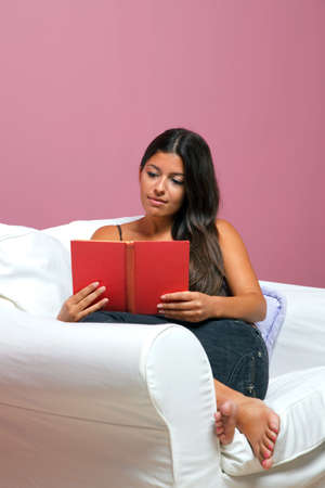 Woman in casual clothing sat in an armchair reading a book Stock Photo - 7056890