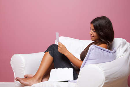 Women sat in an armchair reading a letter, blank envelope to add your own text. Stock Photo - 7056892