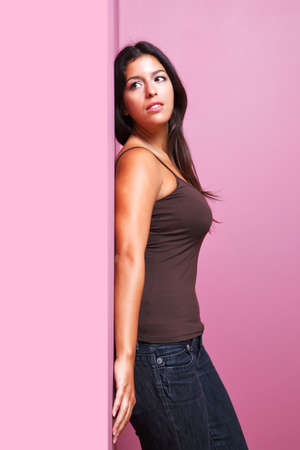 An attractive brunette woman in casual clothing leaning with her back against a wall in the corner of a room. Possible uses could include romance or listening related themes. photo
