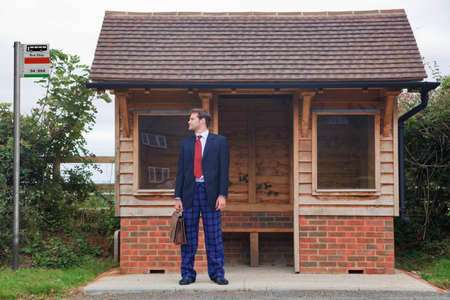 bus stop: Concept image of a businessman standing at a bus stop having missed the last bus, in his rush to get ready he forgot to put his trousers on and is still wearing pyjama bottoms and slippers.