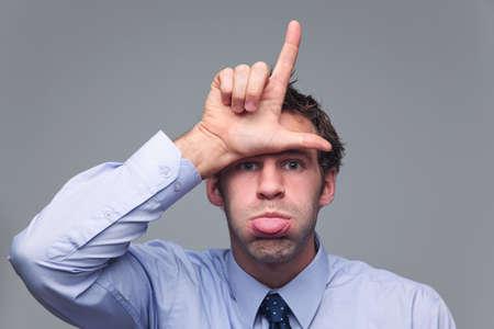 irrespeto: Hombre en camisa y corbata degollar a su lengua y conocer la letra L con su mano como el gesto con la mano para el perdedor Foto de archivo