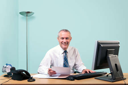 Mature businessman sat at an office desk working on some paperwork smiling to camera. The graphs and text on the documents were made and printed by me. Stock Photo - 7057002
