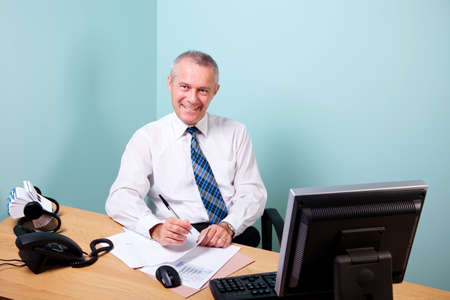 Mature businessman sat at an office desk working on some paperwork smiling to camera. The graphs and text on the documents were made and printed by me. photo