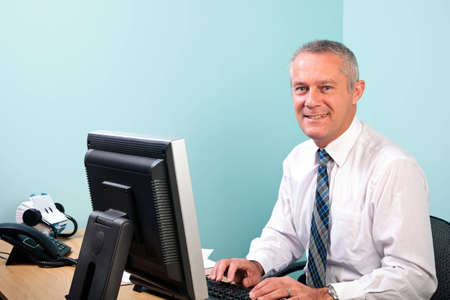 Mature businessman sat at an office desk working on his computer smiling to camera. Stock Photo - 7057010