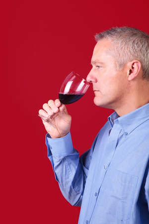 Man smelling a glass of red wine to check its aroma photo