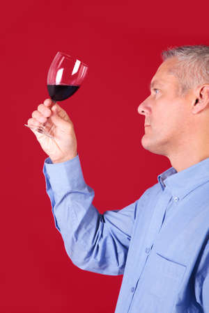 Man checking a glass of red wine for clarity and quality photo