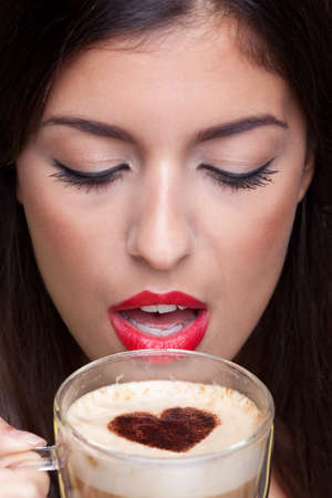 hot lips: Woman drinking a cappuccino coffee with a love heart shape sprinking on top.