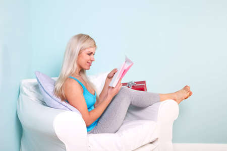 Young blond woman sat in an armchair opening her birthday card. Stock Photo - 7057009